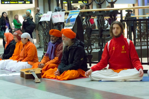 Six (of seven) meditators at Stockholm's Central Train Station. The sign taped to the railing above their heads reads: World Peace Meditation.